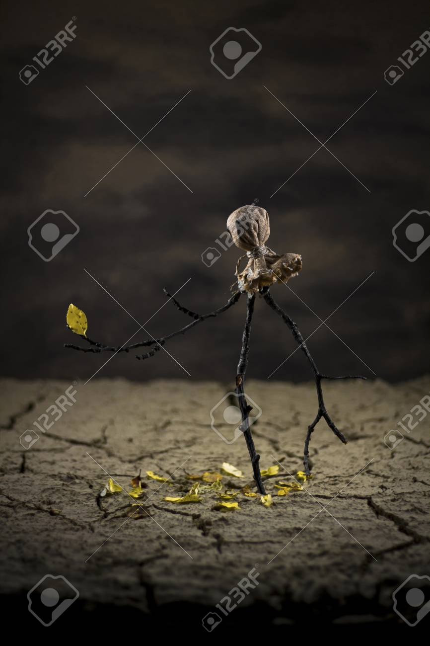 Scarecrow in the desert watchin a yellow leaf on his arm wich supose to fall off Stock Photo - 17485808