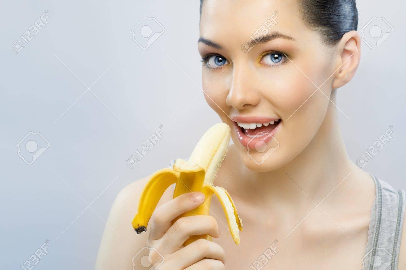 girls eating bannana Stock Photo - a girl with a ripe yellow banana