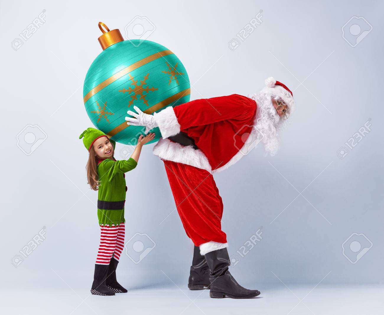 Funny Santa And Elf Holding Together A Huge Christmas Bauble Stock Photo 46636542