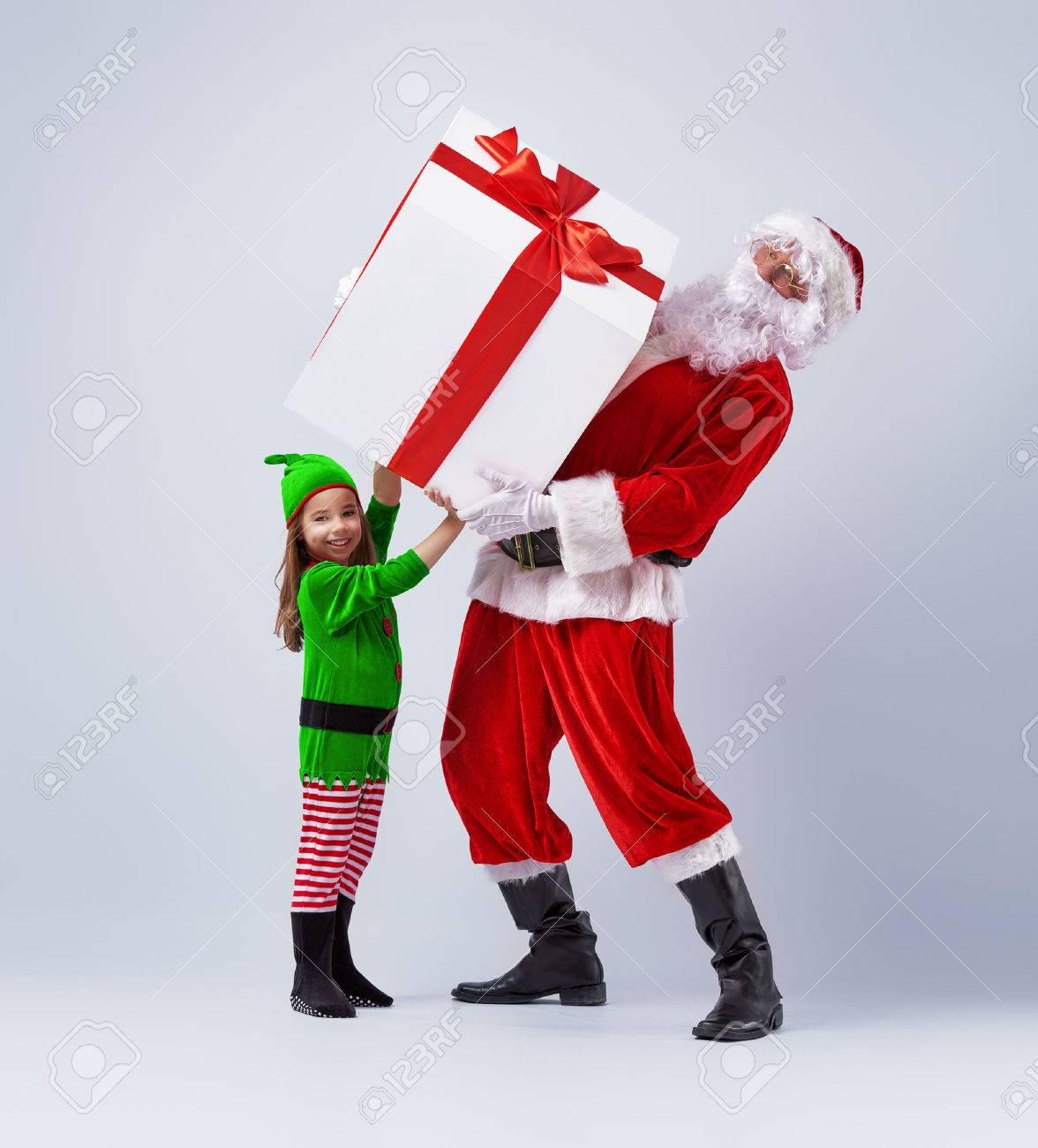 Funny santa and elf holding together a large christmas gift stock funny santa and elf holding together a large christmas gift stock photo 46636744 negle Image collections