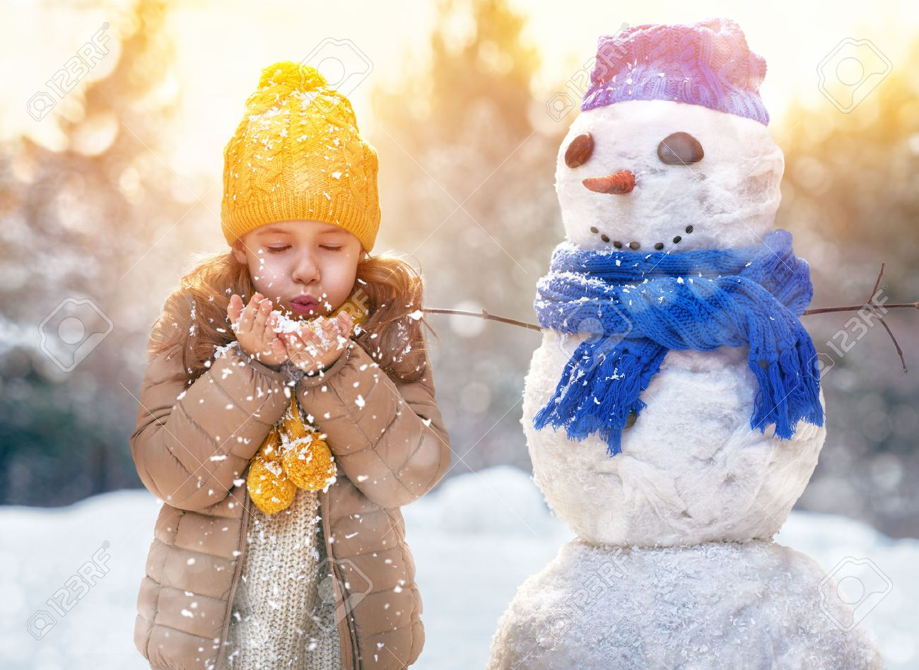 happy child girl plaing with a snowman on a snowy winter walk - 48980752
