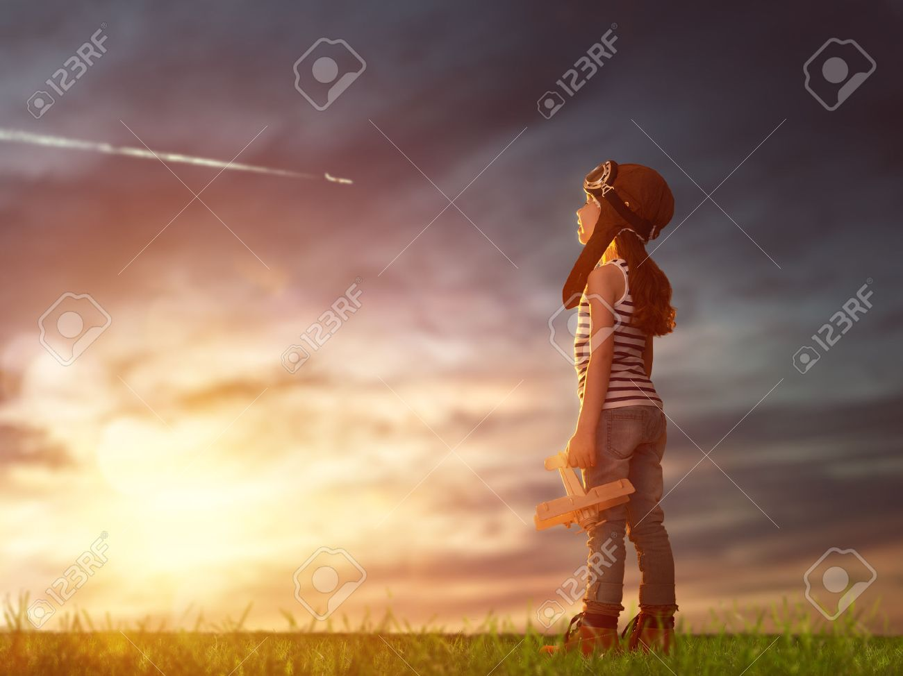 dreams of flight! child playing with toy airplane against the sky at sunset - 50427811