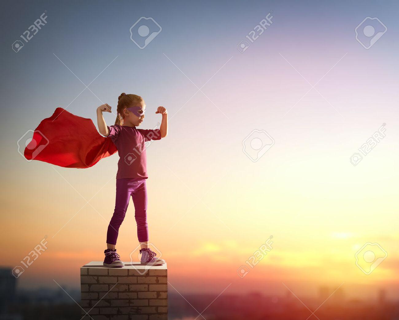Little child girl plays superhero. Child on the background of sunset sky. Girl power concept - 53752799