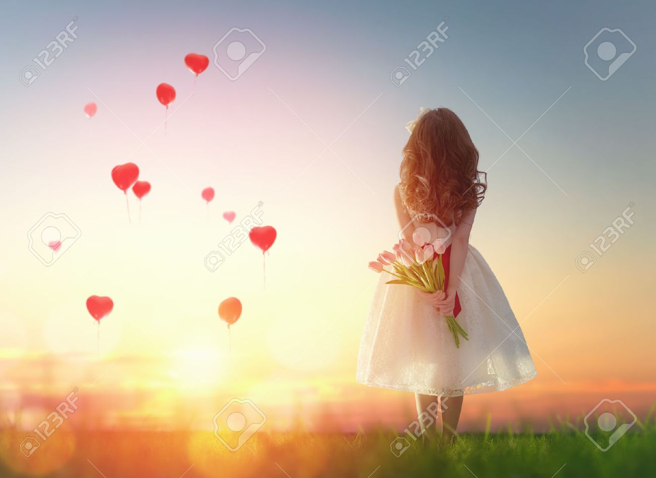 Sweet child girl looking at red balloons. Little child girl holding bouquet of flowers. Balloons in shape of heart flying in the sunset sky. Wedding, Valentine, love concept. - 50846004