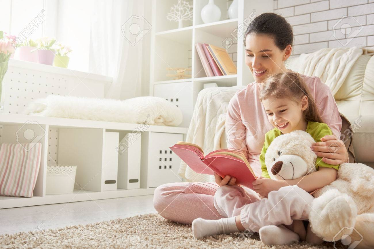 pretty young mother reading a book to her daughter - 51236860