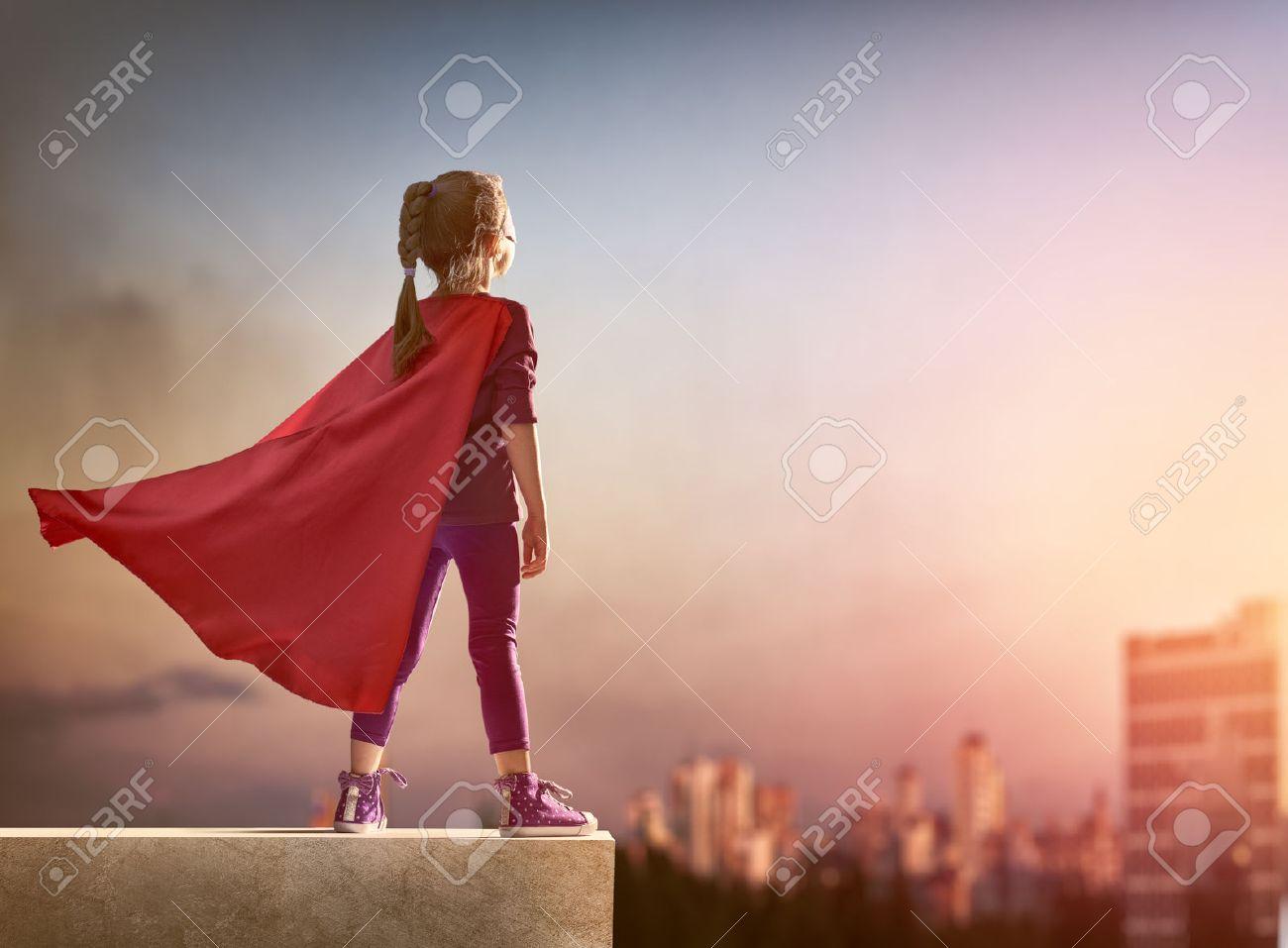 Little child girl plays superhero. Child on the background of sunset sky. Girl power concept - 51236864