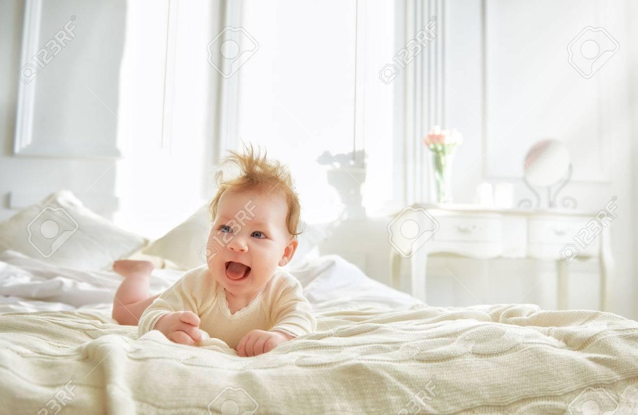 Hermoso Bebé Sonriente Lindo En La Cama En La Habitación. Niño Feliz ...