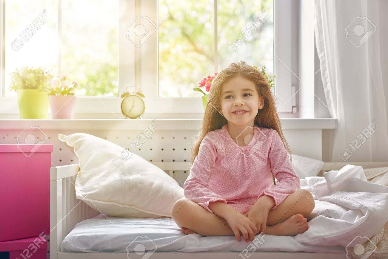 The Child Girl Woke Up And Enjoys The Morning Sun Stock Photo