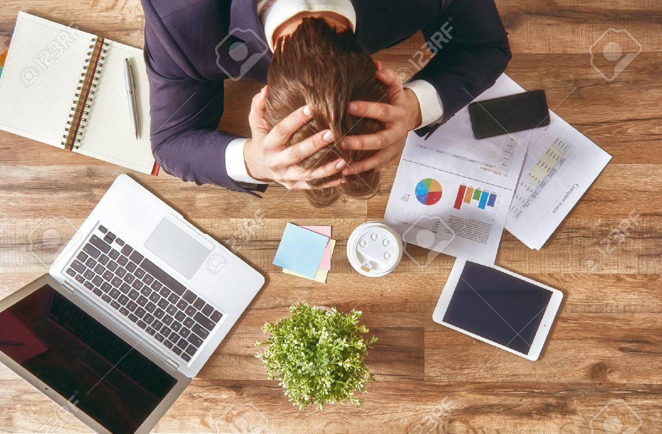 businessman in panic. a young man sits at his Desk and holds his hands on his head. - 51923322