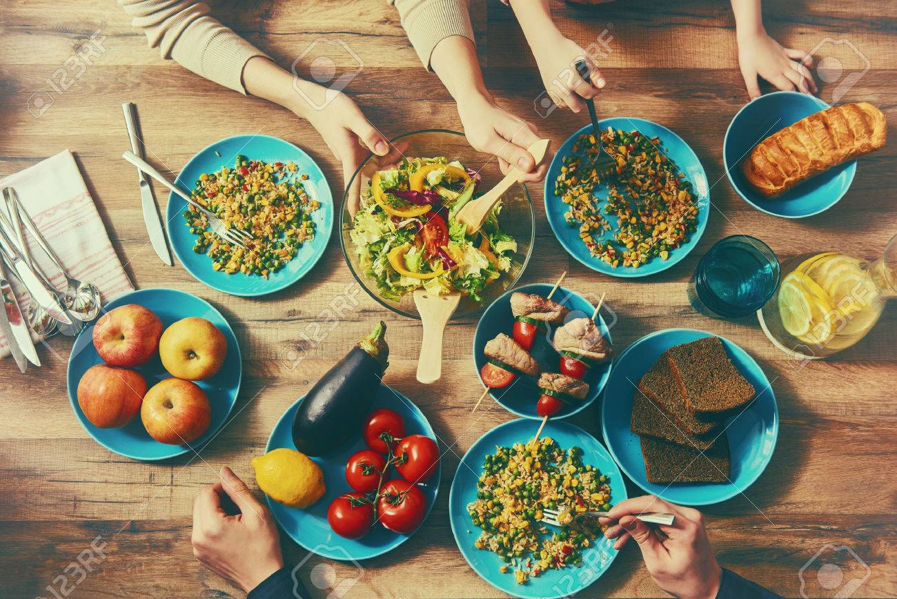 Top view of family having dinner together sitting at the rustic wooden table. Enjoying family dinner together. - 52154689