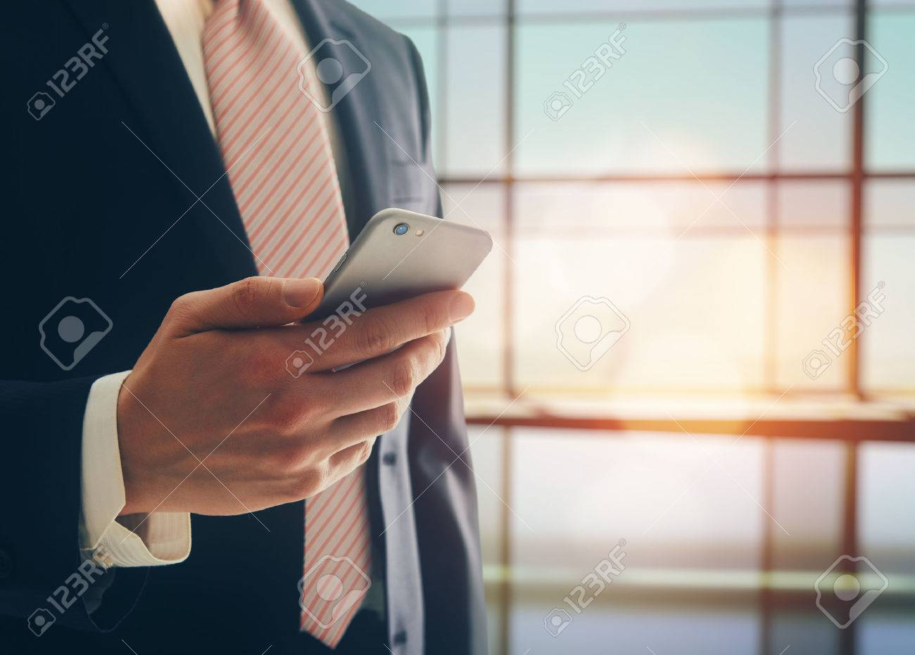 Portrait of a confident man. Entrepreneur working on phone while standing in modern office interior. Intelligent male lawyer holding phone. - 52328787