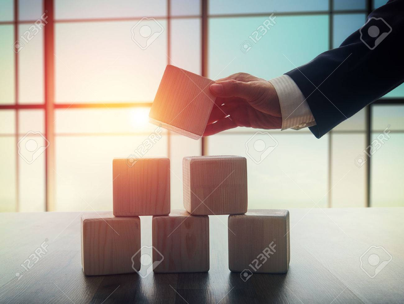 The concept of planning in business. Wooden cubes on a desk in the office. The concept of leadership. Hand men in business suit holding the cubes. - 52484027