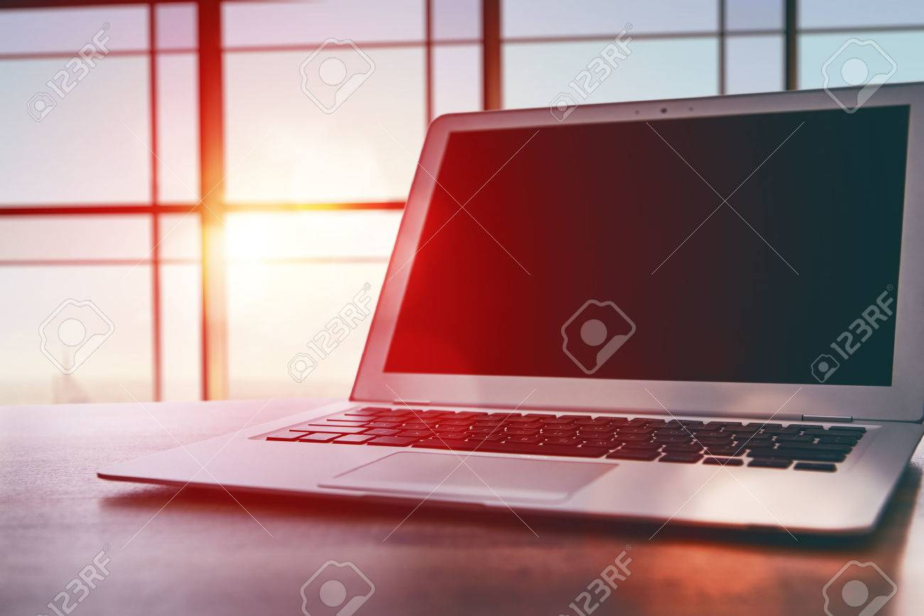 Laptop with dark screen on table in office - 52484131
