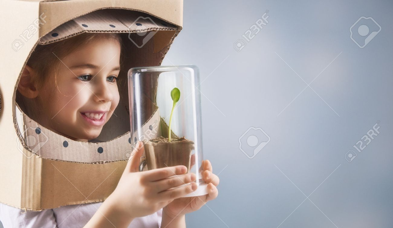 Child is dressed in an astronaut costume. Child sees a sprout in a glass case. The concept of environmental protection. - 53480414