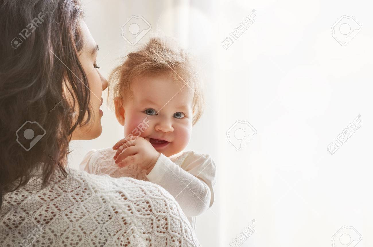 happy loving family. mother playing with her baby in the bedroom. - 54018509