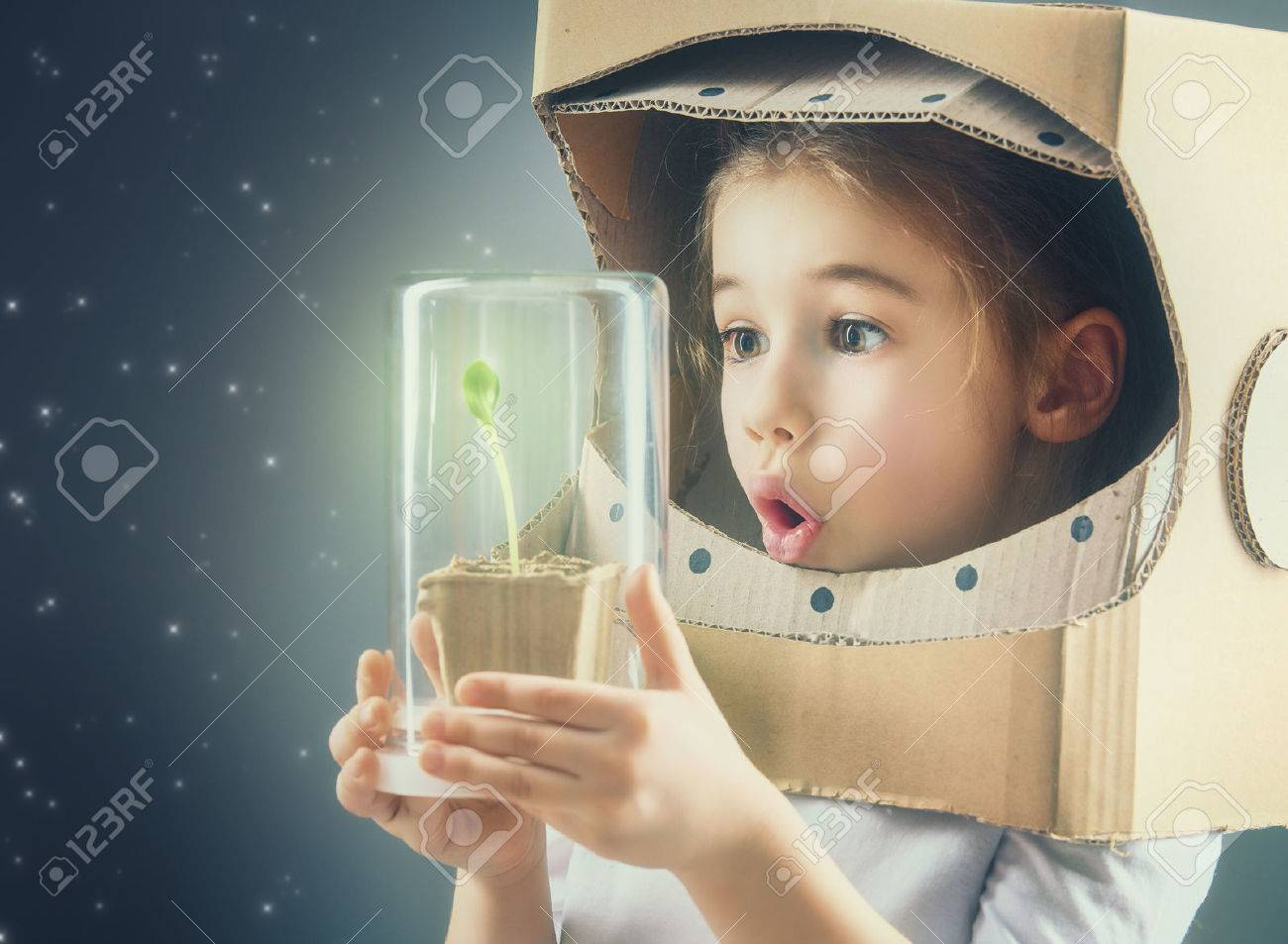 Child is dressed in an astronaut costume. Child sees a sprout in a glass case. The concept of environmental protection. - 54061250
