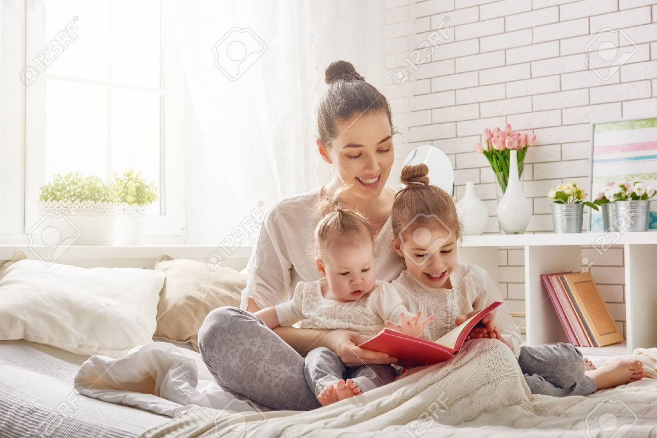 happy loving family. pretty young mother reading a book to her daughters - 54018592