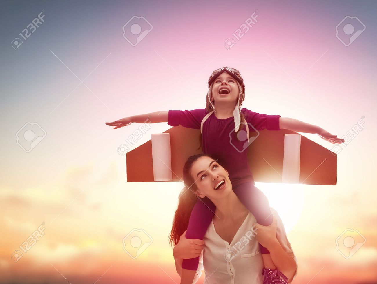Mother and her child playing together. Little child girl plays astronaut. Child in an astronaut costume plays and dreams of becoming a spaceman. Happy loving family having fun. - 54018619