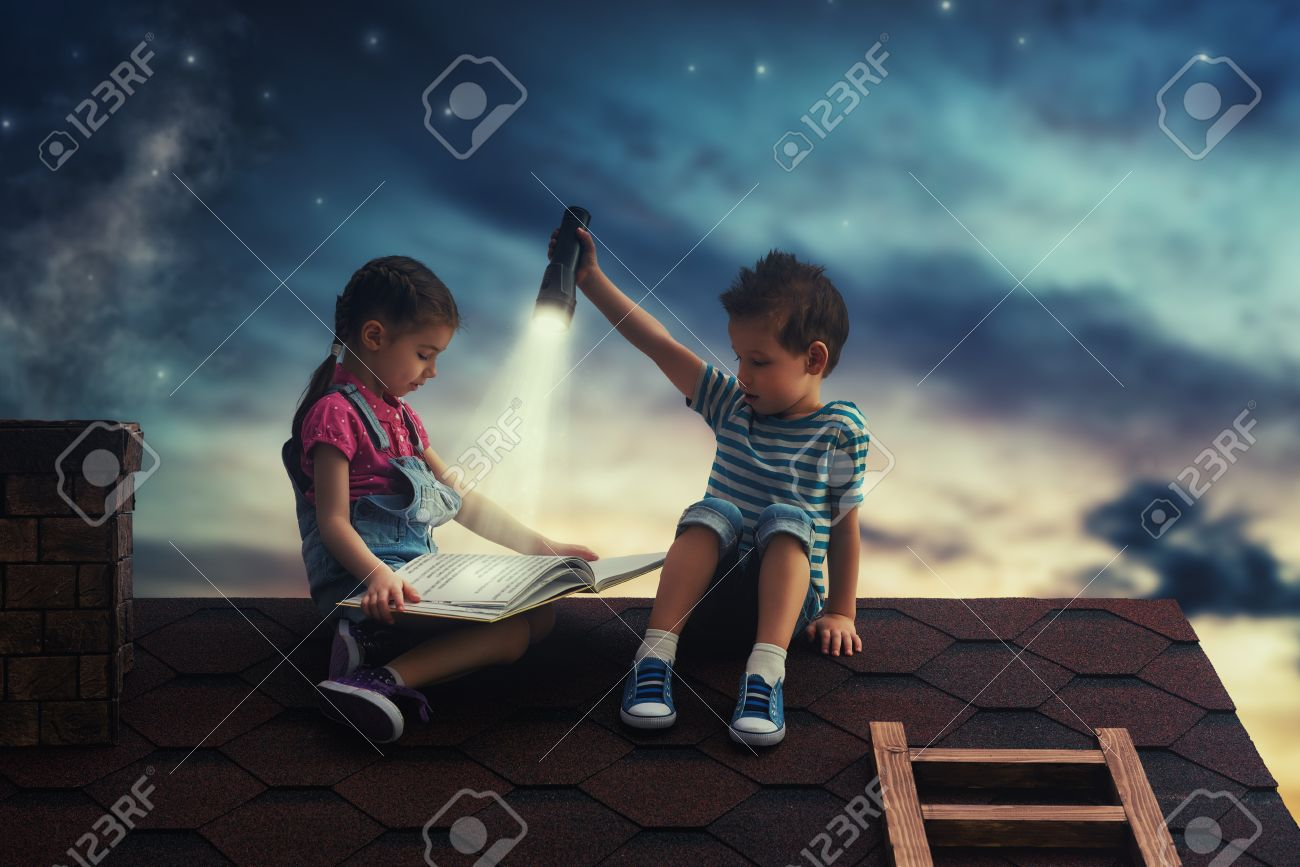 Children reading a book sitting on the roof of the house. Boy and girl reading by the light of a flashlight at night. - 54722901