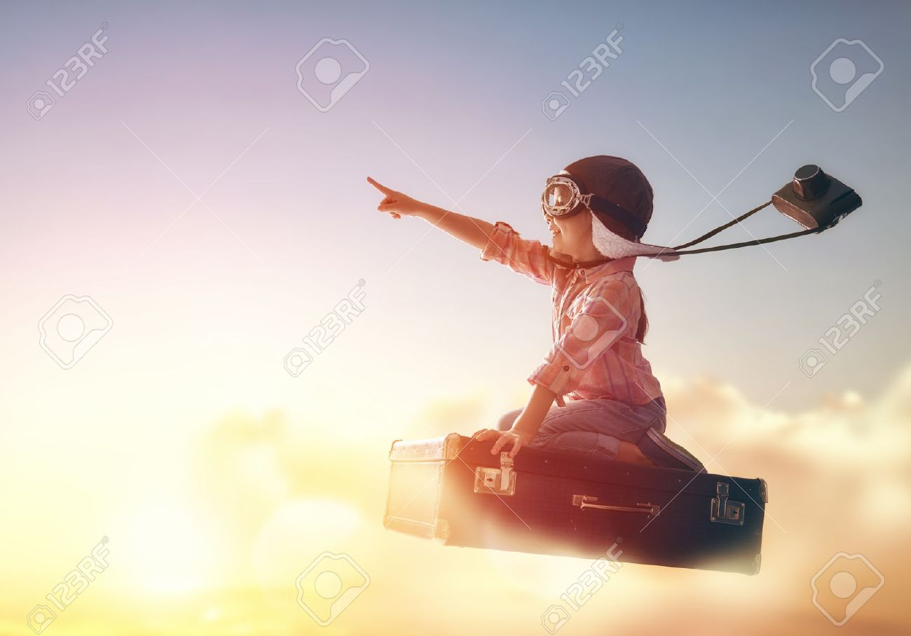 Dreams of travel! Child flying on a suitcase against the backdrop of a sunset. - 54723273