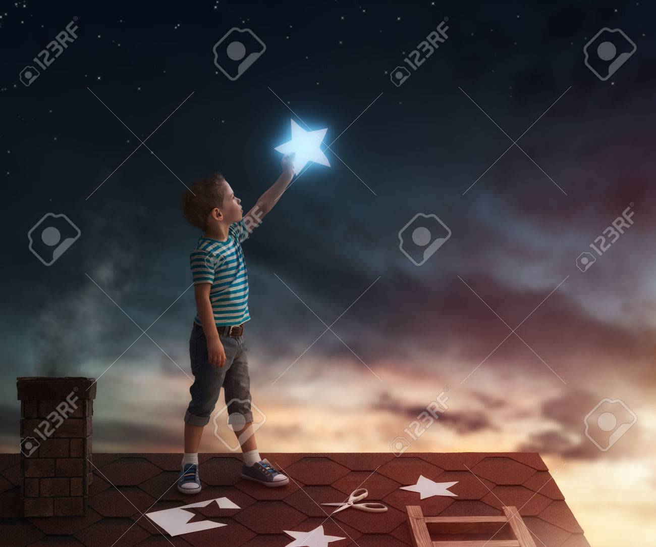 Fairy tale! The child hanging the stars in the sky. Boy on the roof cuts out stars. - 54723668