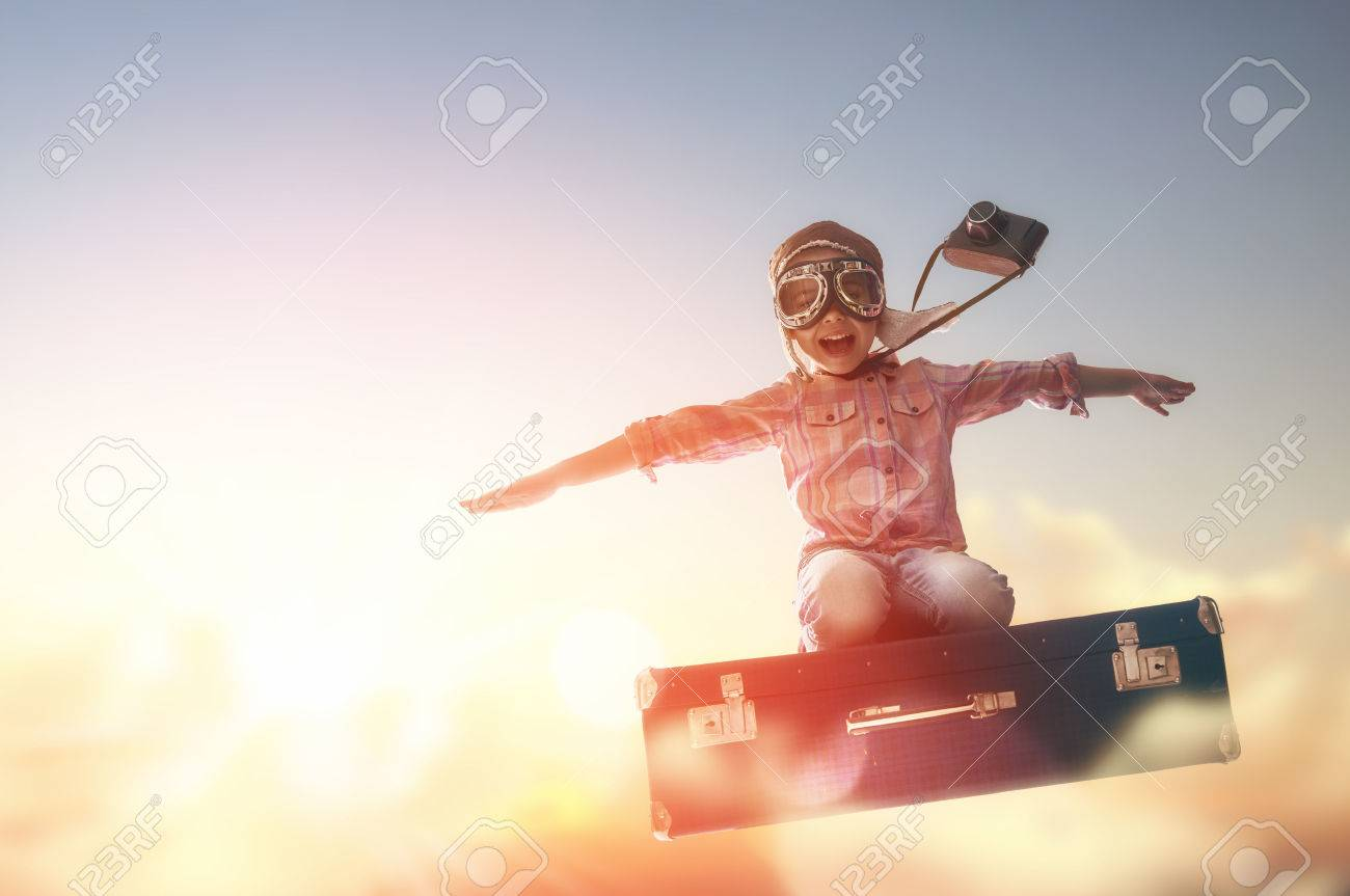 Dreams of travel! Child flying on a suitcase against the backdrop of a sunset. - 54723727