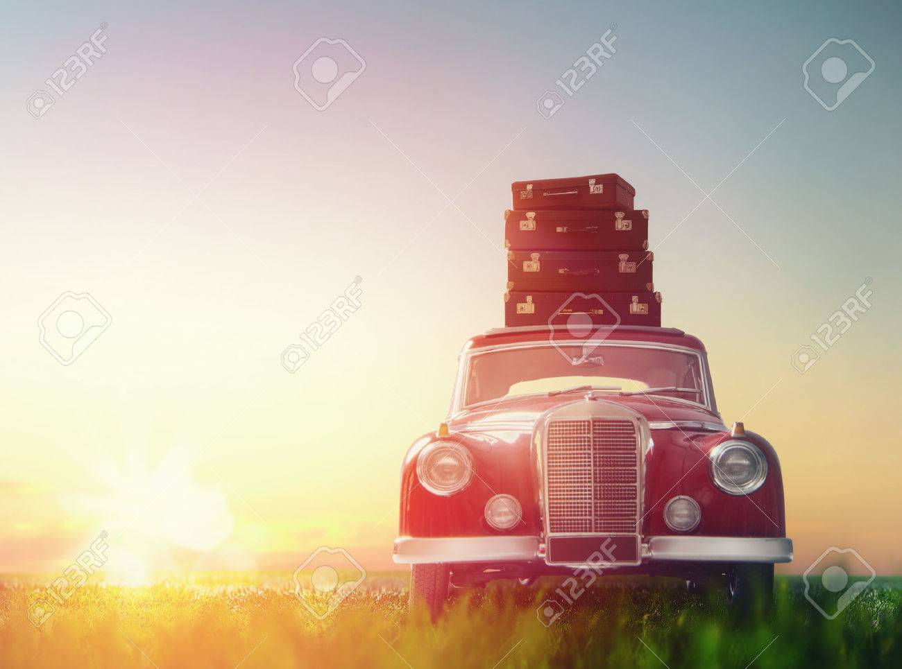 Toward adventure! The suitcases are on the roof of a vintage car. - 55145531