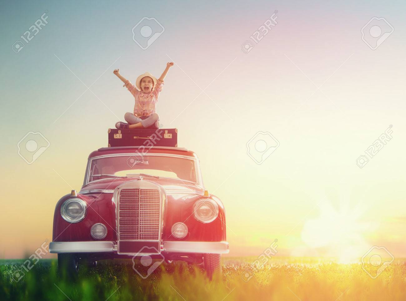 Toward adventure! Girl relaxing and enjoying road trip. Happy child girl sitting on roof of vintage car. - 55594998