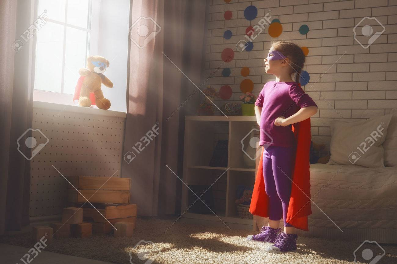 Little child girl plays superhero. Child plays with her friend a Teddy bear. Girl power concept. - 56618646