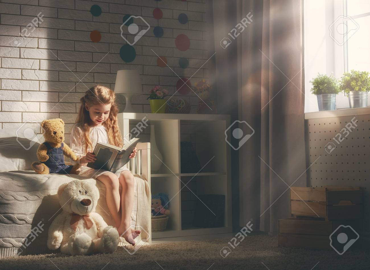 Cute little child girl reading a book. Kid girl sitting in her bed. - 56780888