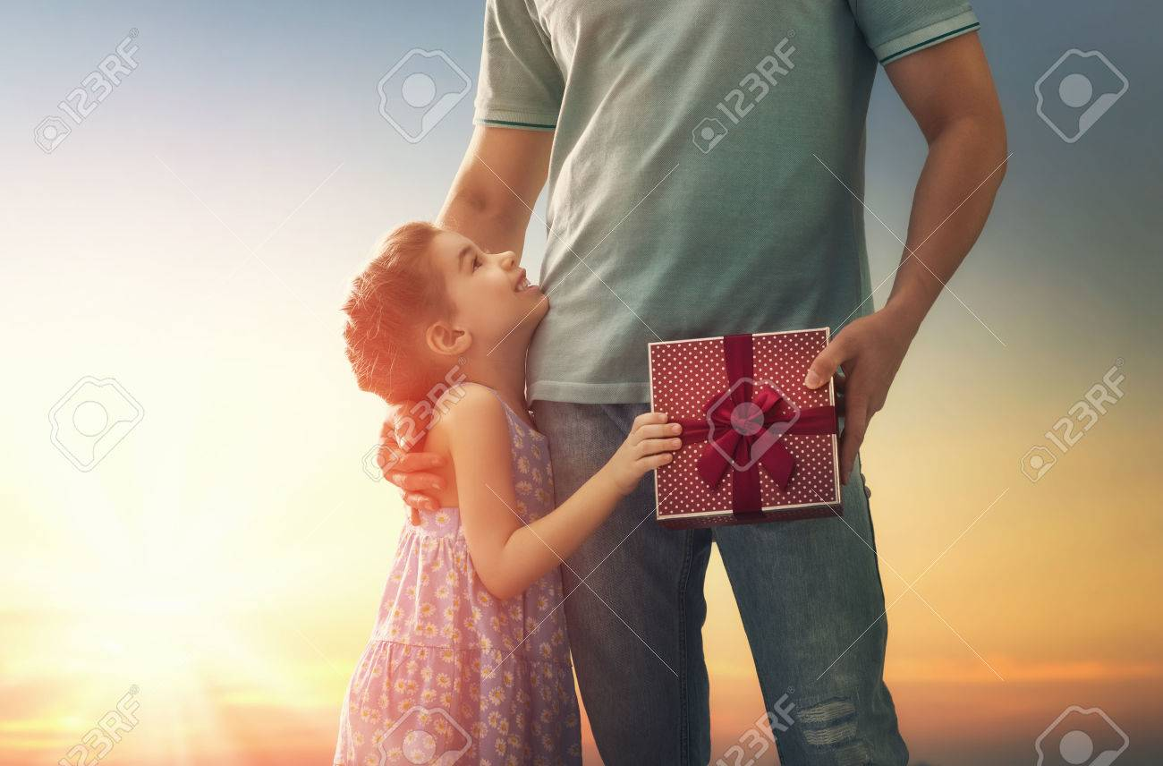 Happy loving family and Father's Day. Father and his daughter. Cute child girl gives a gift to dad. - 56909391