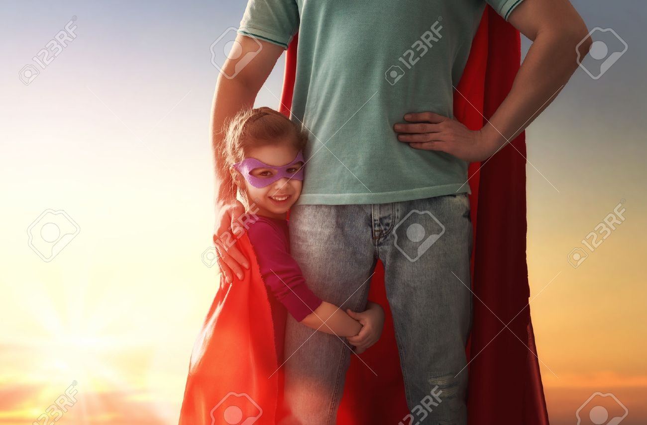 Happy loving family. Father and his daughter child girl playing outdoors. Daddy and his child girl in an Superhero's costumes. Concept of Father's day. - 57628706