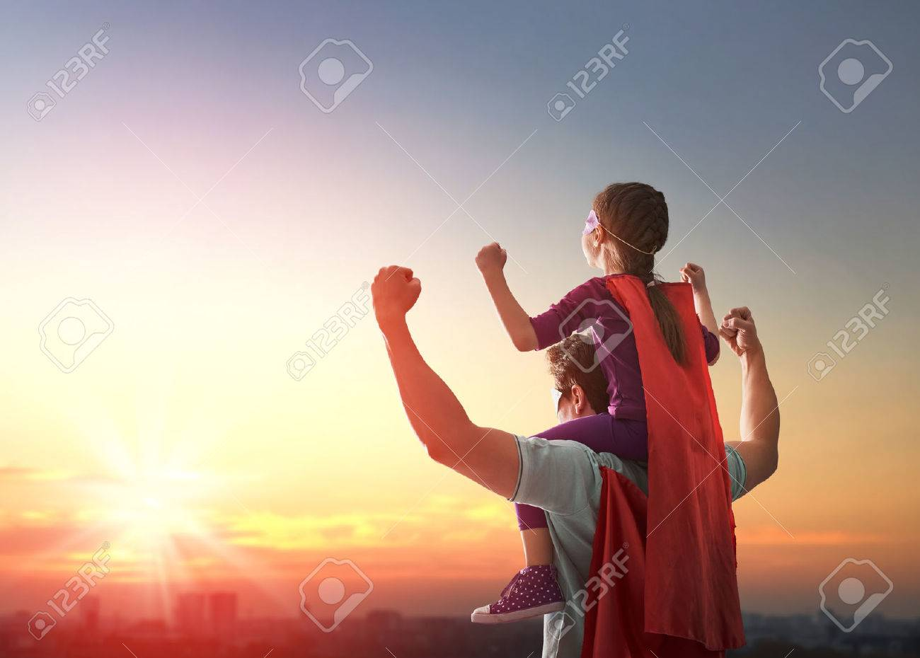 Happy loving family. Father and his daughter child girl playing outdoors. Daddy and his child girl in an Superhero's costumes. Concept of Father's day. - 57628722