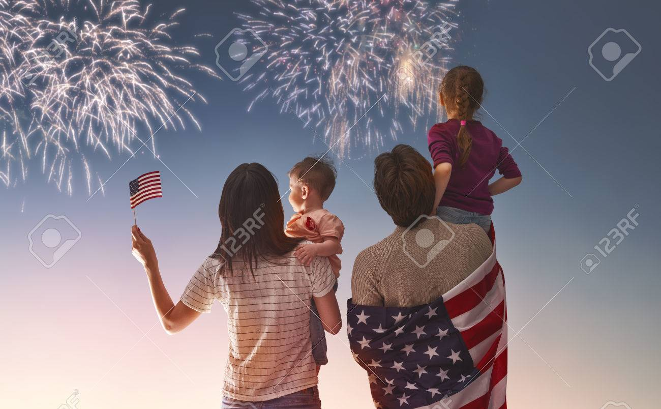 Patriotic holiday. Happy family, parents and daughters children girls with American flag outdoors. USA celebrate 4th of July. - 58218222