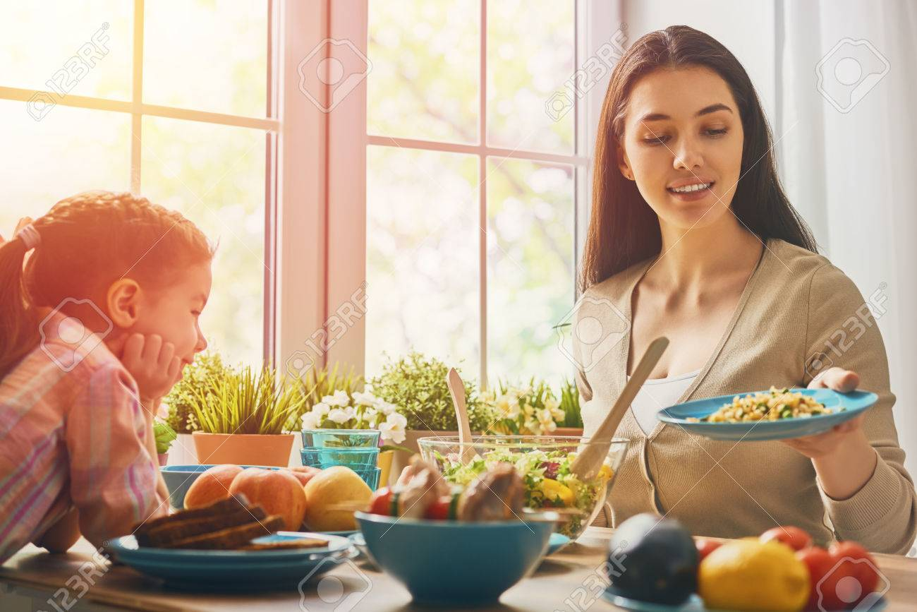 Happy family having dinner together sitting at the rustic wooden table. Mother and her daughter enjoying family dinner together. - 59181516