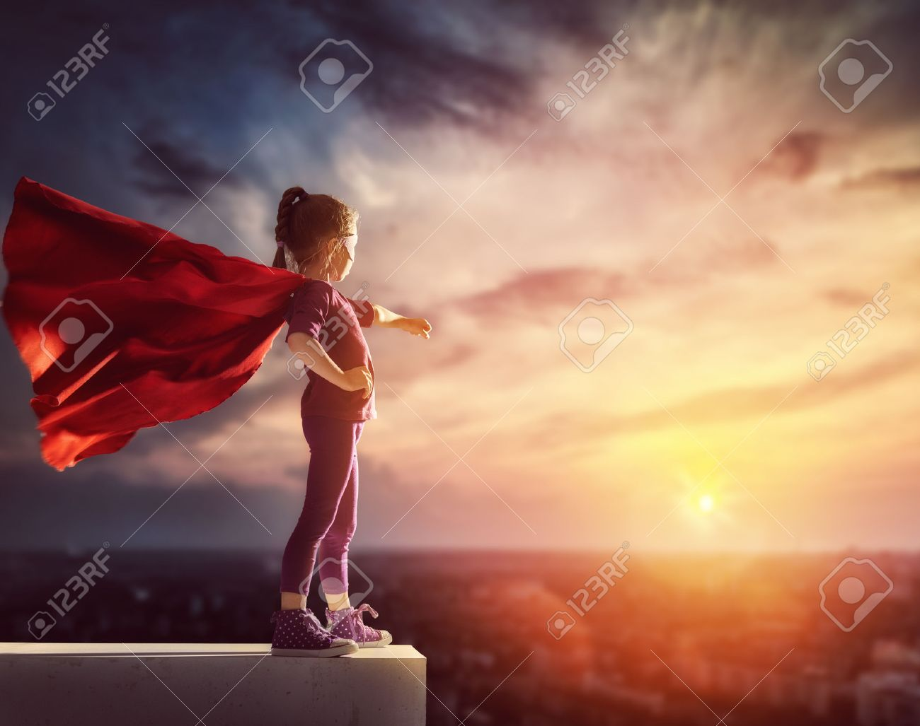Little child plays superhero. Kid on the background of sunset sky. Girl power concept - 59181530