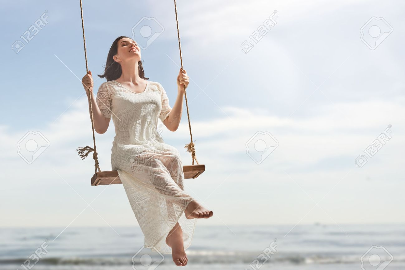 beautiful young woman on a swing on summer day outdoors - 61034052