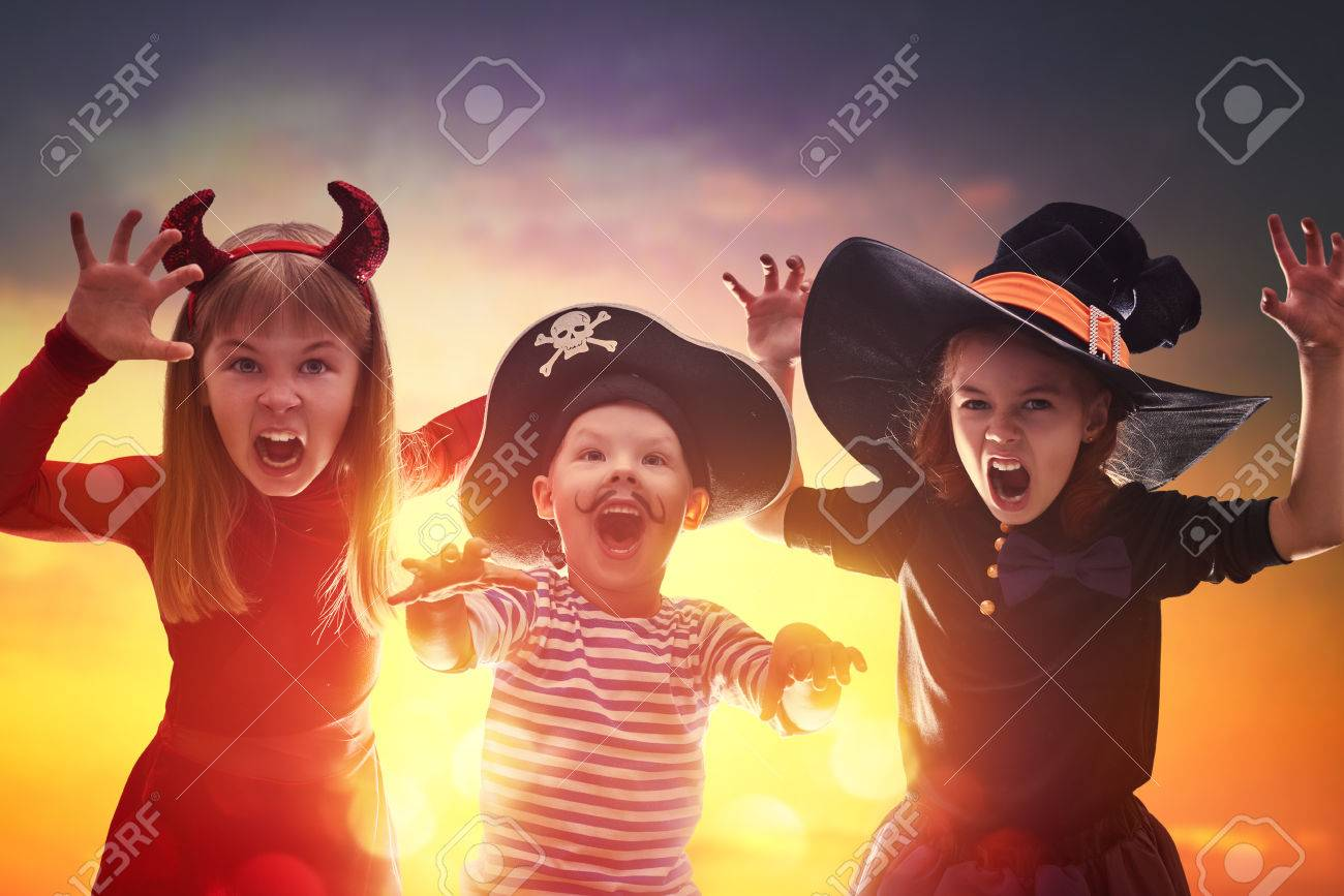 Happy brother and two sisters on Halloween. Funny kids in carnival costumes outdoors. Cheerful children on sunset background. - 62765541