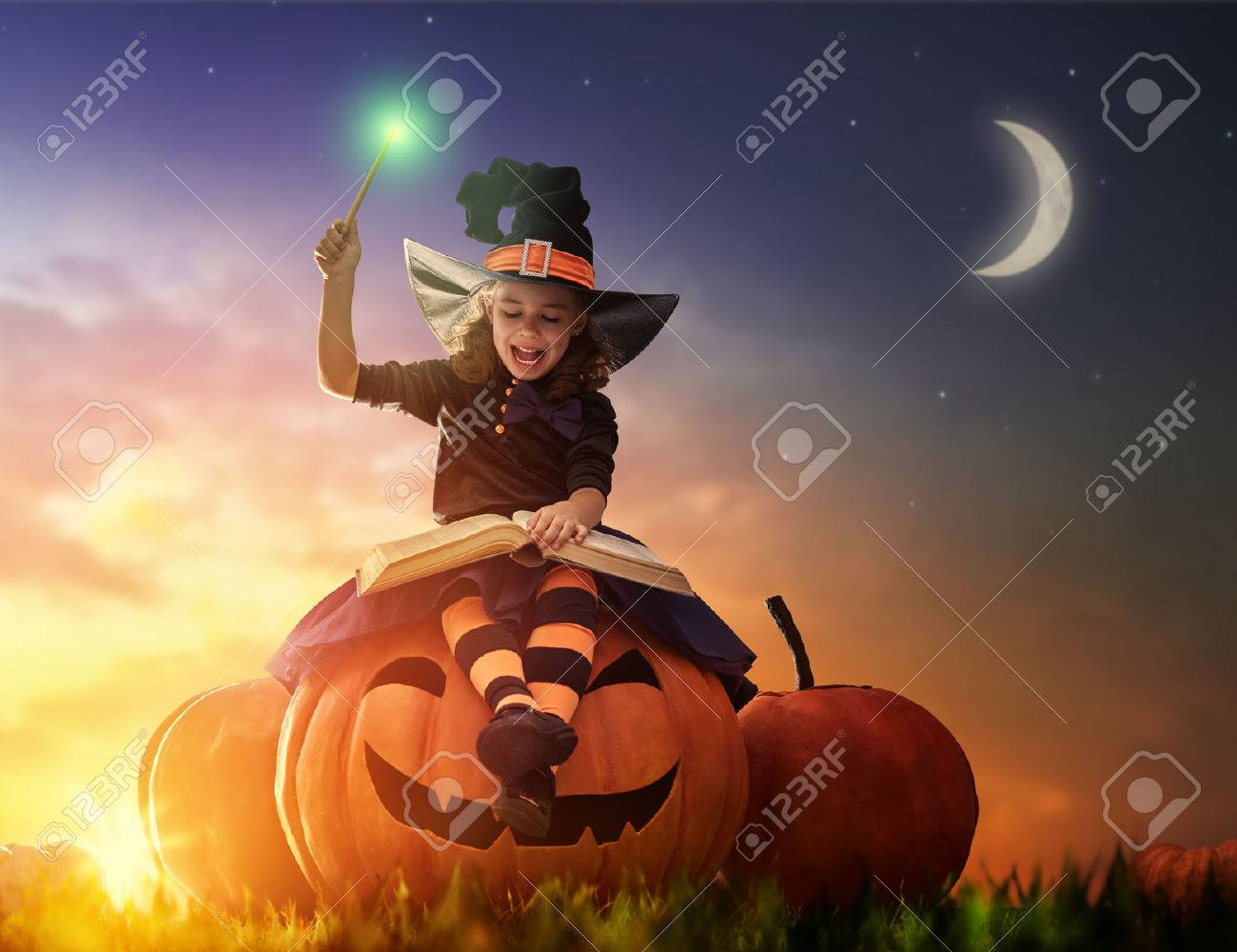 Happy Halloween! Cute cheerful little witch with a magic wand and book of spells. Beautiful child girl in witch costume sitting on the big pumpkin, conjuring and laughing. - 62765695