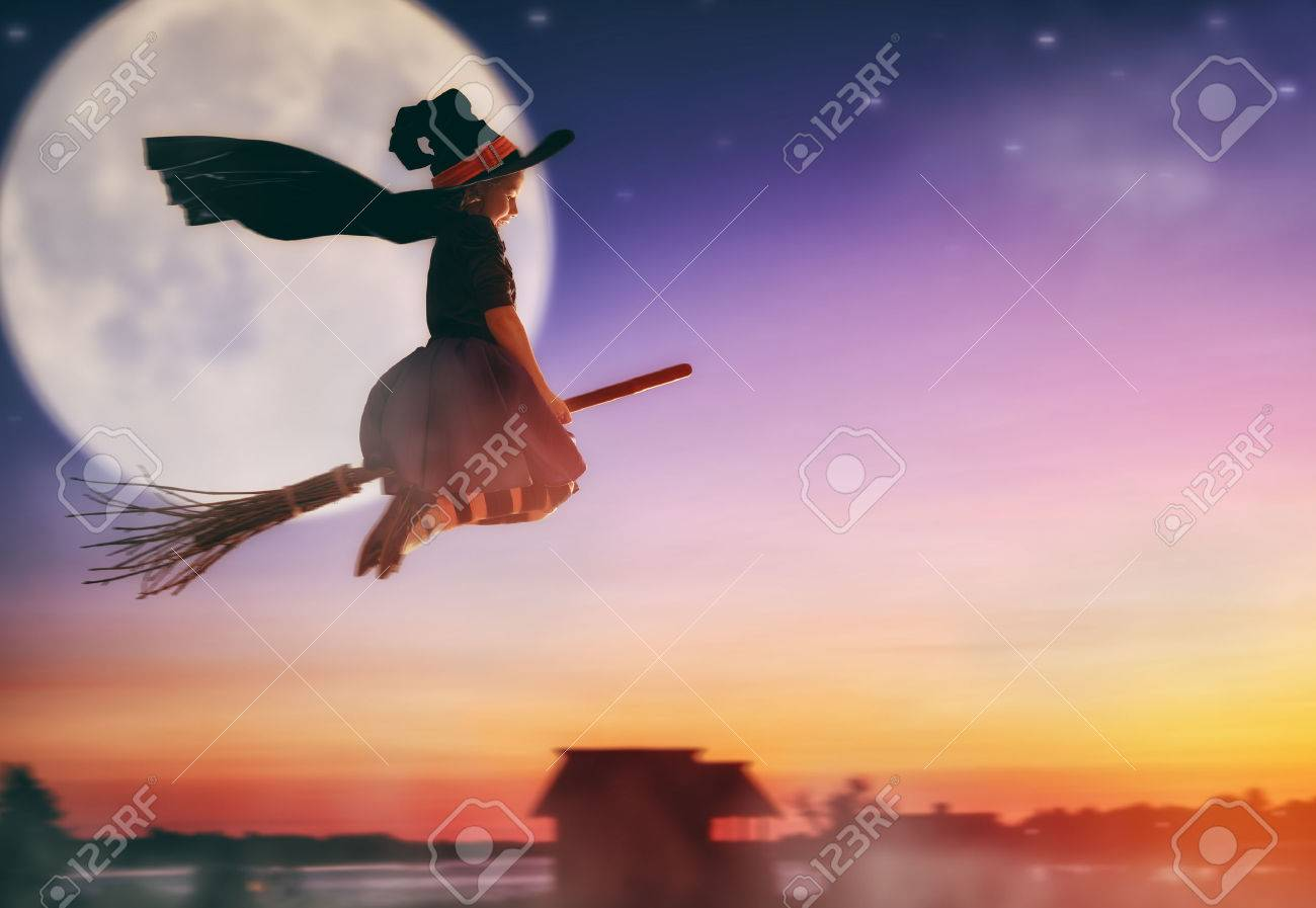 Happy Halloween! Cute little witch flying on a broomstick. Beautiful young child girl in witch costume outdoors. - 62992008