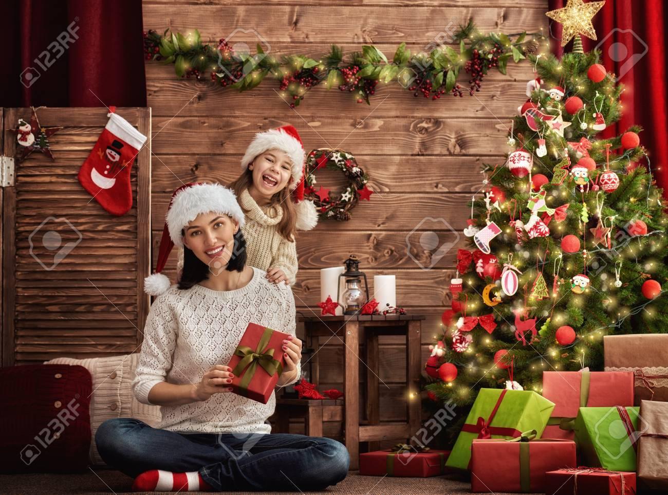 Fröhliche Weihnachten! Mutter und ihre Tochter Kind Mädchen Weihnachtsgeschenke austauschen