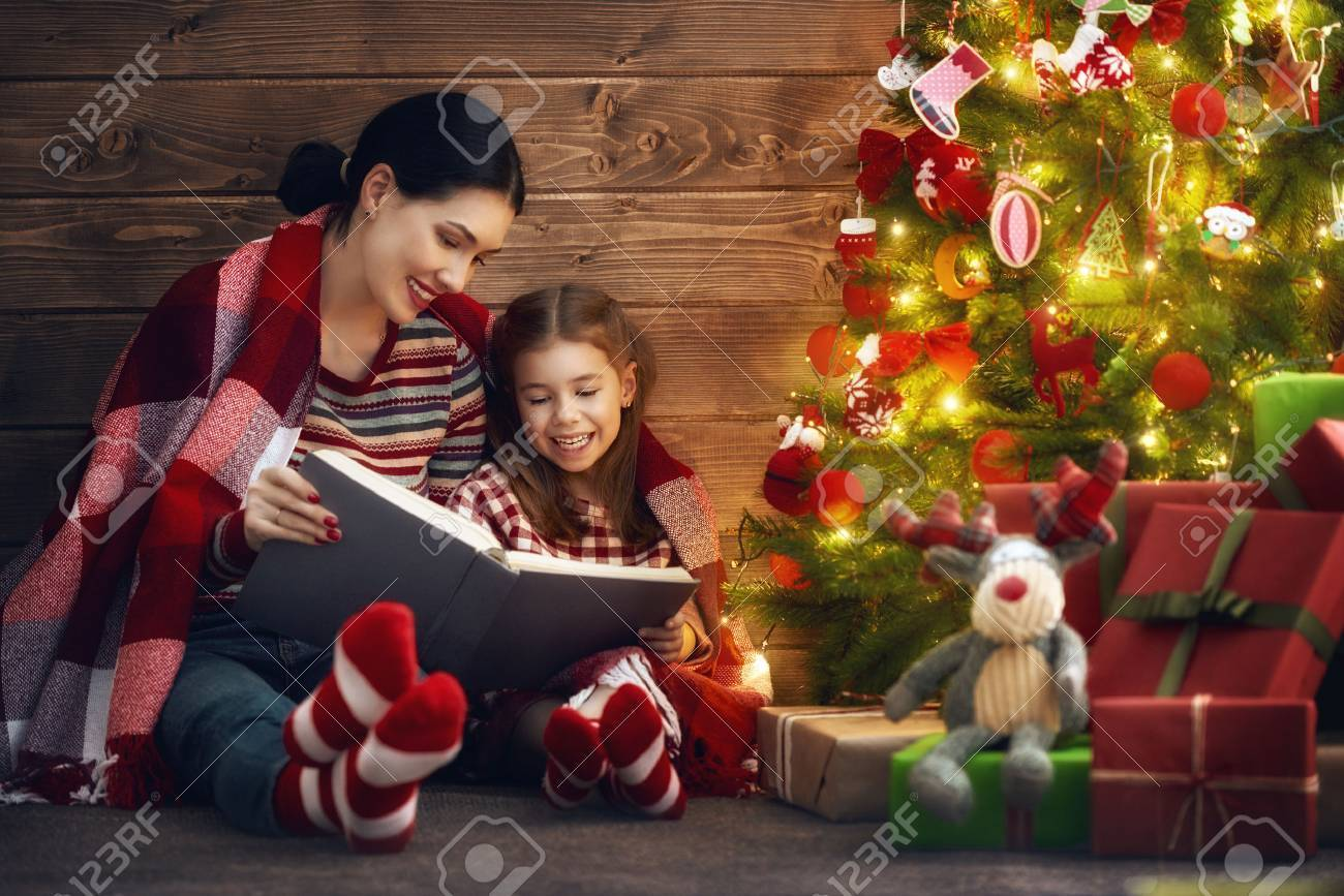 Merry Christmas And Happy Holidays! Pretty Young Mom Reading.. Stock ...