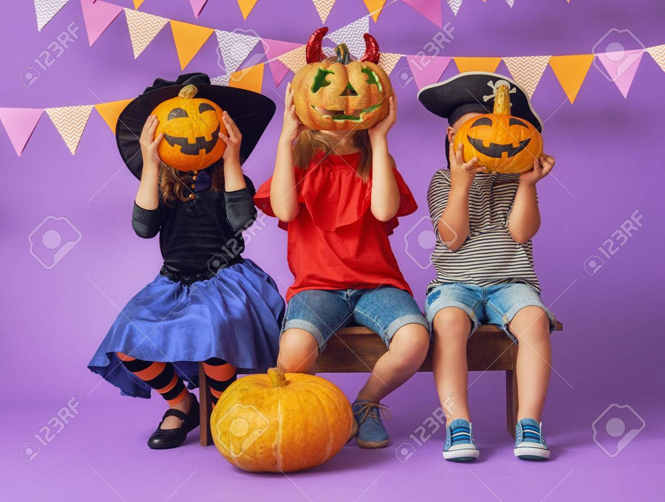 happy brother and two sisters at halloween. funny kids in carnival