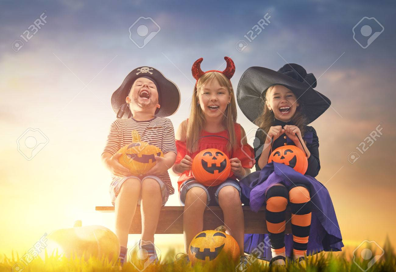 Happy brother and two sisters at Halloween. Funny kids in carnival costumes outdoors. Cheerful children and pumpkins on sunset background. - 85131483