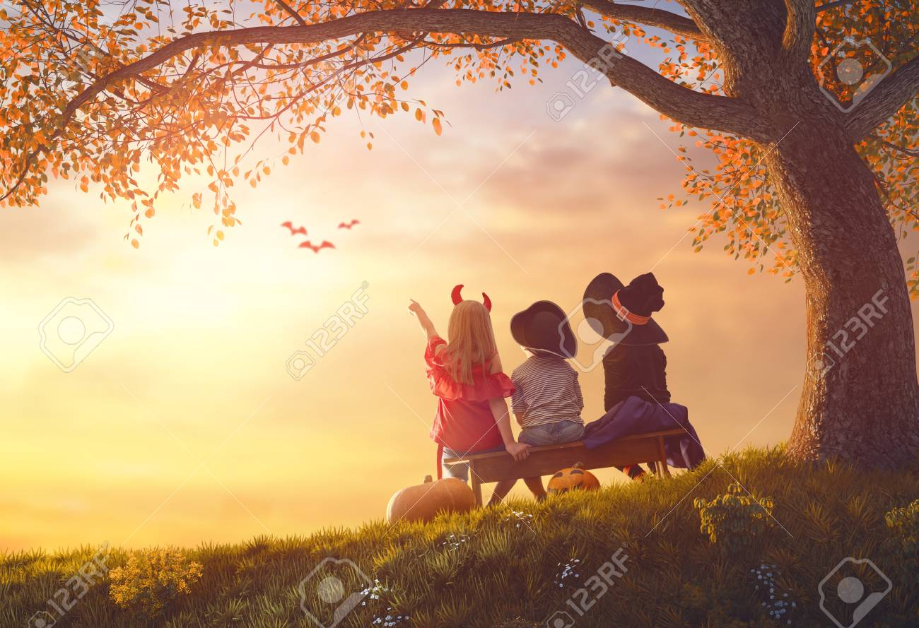 Happy brother and two sisters at Halloween. Funny kids in carnival costumes outdoors. Cheerful children and pumpkins on sunset background. - 85200920