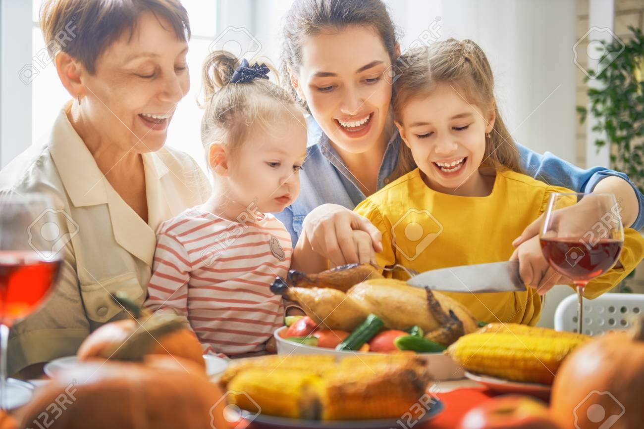 Happy Thanksgiving Day! Autumn feast. Family sitting at the table and celebrating holiday. Traditional dinner. Grandmother, mother and daughter. - 89098058