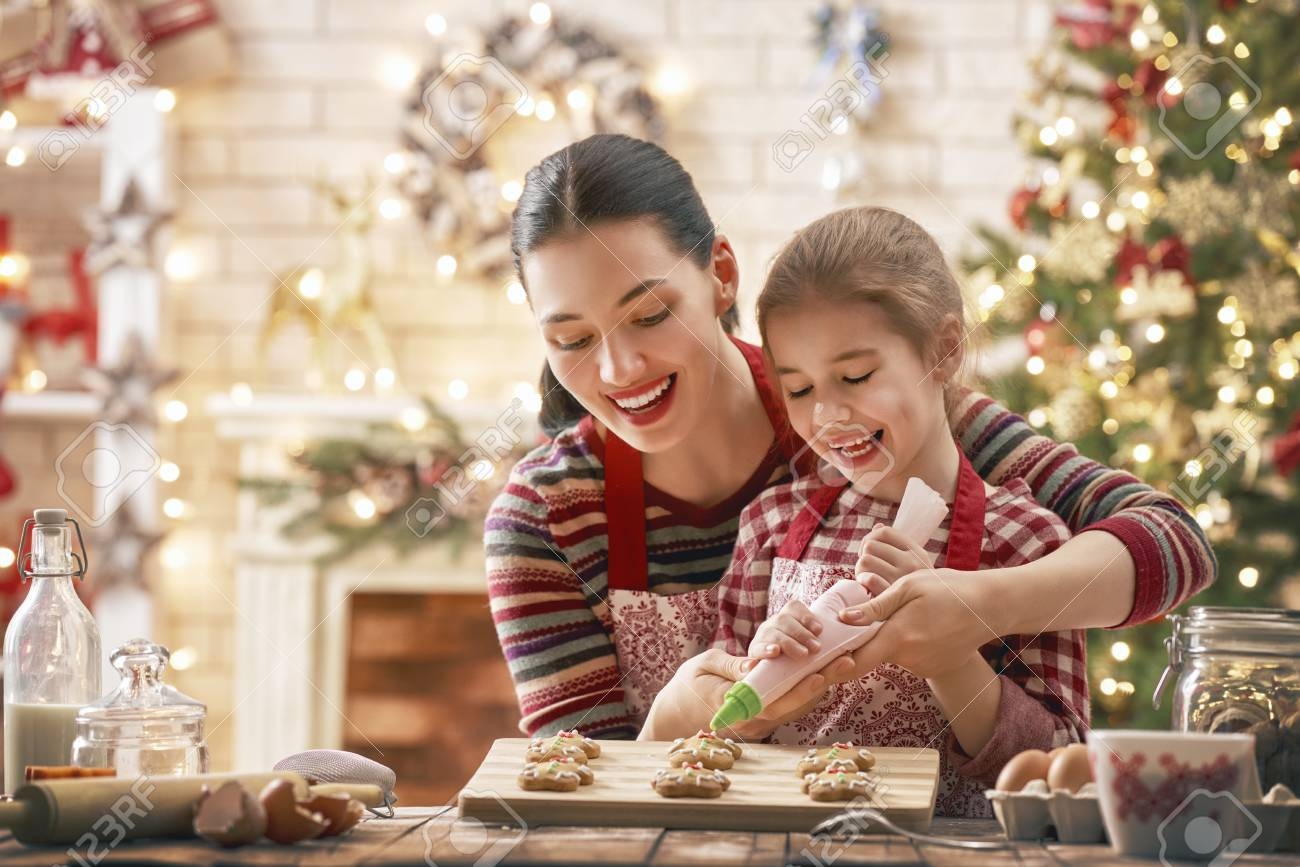 Merry Christmas and Happy Holidays. Family preparation holiday food. Mother and daughter cooking cookies. - 90084627