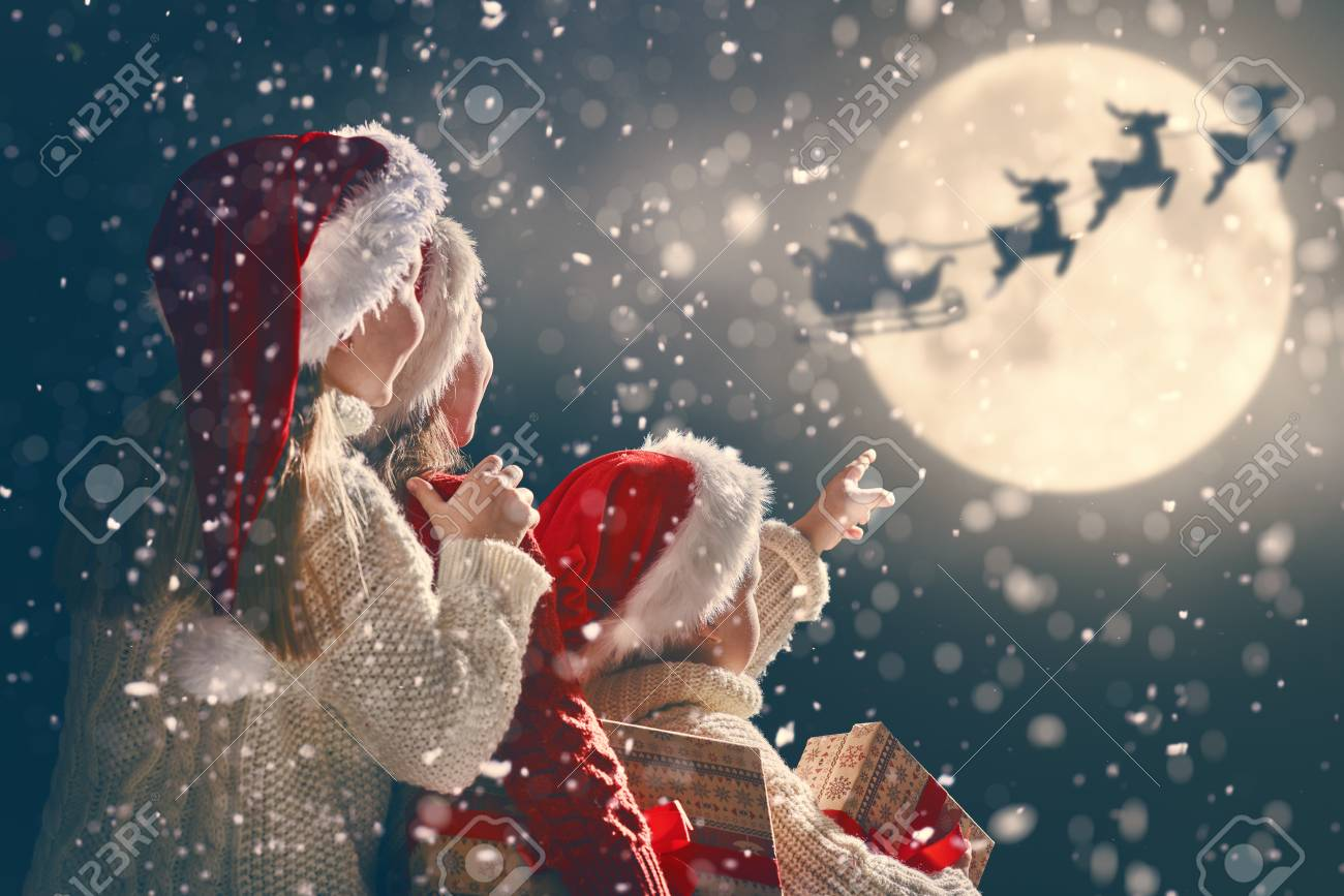 Merry Christmas and happy holidays! Cute little children with xmas presents. Santa flying in his sleigh against moon sky. Kids enjoying the holiday with gifts on dark background. - 90145786