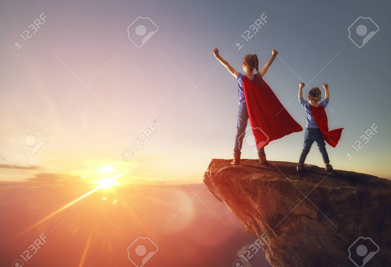 Two little children are playing superhero. Kids on the background of sunset sky. Girl power concept - 94499393