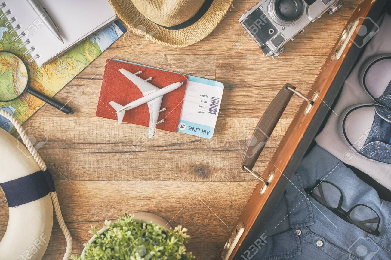 Go on an adventure! The map, suitcase, passports, tickets and the camera on a wooden table. Top view. - 95372616